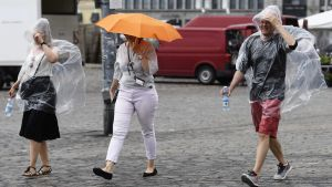 Tre personer går ute i regnet i Helsingfors. Två av dem bär en engångsregnjacka och en av dem går under ett paraply.