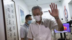 Premiärminister Lee vinkade till pressfotograferna då han länade partikansliet efter att de preliminära resultaten offentliggjorts.