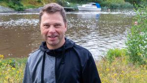 En leende man vid en å. Vit motorbåt ankrad i bakgrunden.