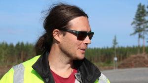En man med solglasögon och långt mörkt hår i en hästsvans står i en skogsöppning.