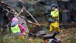 En flicka och en pojke från dagisgruppen Valhajarna bygger en koja av kvistar och träbitar vid en klippa på Drumsö.