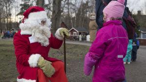 Julgubben sitter och pratar med en flicka i rosa halare och ljusröd mössa. Det är helt snöfritt på gräsmattan och marken omkring dem.