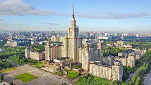 Ett stort byggnadskomplex med en tornbyggnad i mitten. Tornet kröns av en röd stjärna.