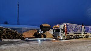 En hjullastare lastar en lastbil med flis.