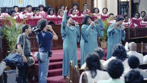 The Barrett Sisters ja gospelkuoro esiintymässä kirkossa, kuvausryhmä seuraa. Pressikuva dokumentista Say Amen, Somebody (1982)