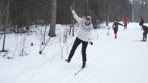 Skidåkare glider på en skida i skidspåret