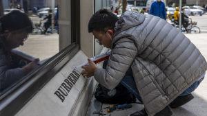 En man klädd i grått hukar sig och applicerar kitt på en skylt som han reparerar.