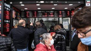 Kunder står och tittar på skärmar på ett valutakontor.