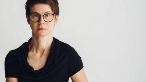 Regissören Milja Sarkola sitter på en trästol mot en vit bakgrund.