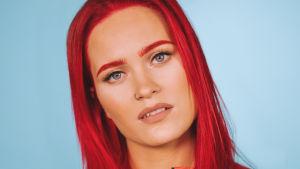 Sannilla on kirkkaan punaiset hiukset ja vaatteet. Tausta on turkoosi.