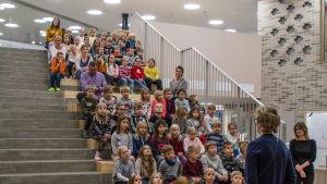 Morgonsamling i en skola, eleverna sitter i trappan och rektorn står med ryggen vänd mot kameran i förgrunden