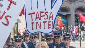 """En kvinna i ett demonstrationståg håller upp skylten """"tafsa inte""""."""