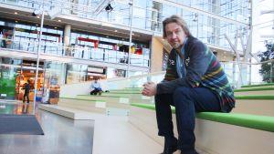Journalisten Saska Saarikoski sitter på en bänk i Sanoma huset.