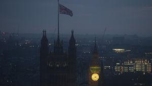 Storbritanniens flagga svajar i tornet i ett dimmigt London med en rosa-mörkblå soluppgångshimmel.