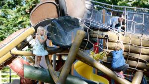 Tre barn klättrar i en lekpark.