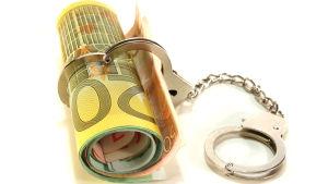 En rulle med eurosedlar som har en handboja runt sig.