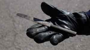 bild på en hand som håller upp en kniv
