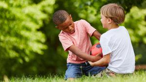 Två småpojkar slåss om en fotboll
