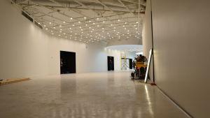 Foajen till konstmuset Amos Rex. I taket hänger flera små lampor som skänker ett milt sken över golvet.