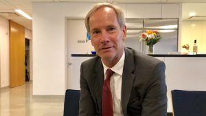 Porträtt av Sveriges FN-ambassadör Olof Skoog, brundbränd, leende, med röd slips på sned.