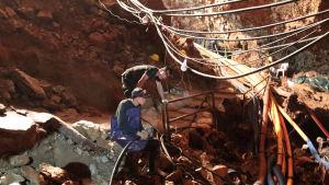 En massa slangar och två räddningsarbetare jobbar med att pumpa ut vatten ur Tham Luang-grottorna.