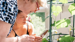Eläkeikäinen nainen ja tytärpuolensa katsovat kännykästä ruukku asvin hoito-ohjetta tms. tietoa kasveista, kasvin edessä.
