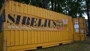 en gul container med en banderoll i en park
