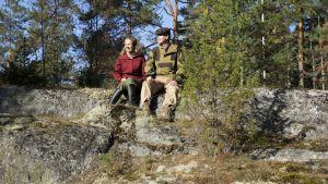 Adela Pajunen ja Marko Leppänen istuvat kalliolla auringossa.