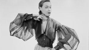 Nainen haute couture -asussa, jossa on isot, läpinäkyvät hihat.