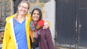 Två kvinnor, en i gul regnrock andra med rutig halsduk. Den med gul rock är längre och äldre och håller sin ena arm om den andra. De är glada och ler stort.