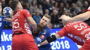 Teemu Tamminen stoppas av en vitrysk försvarare.