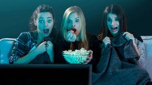 Tre ungdomar som tittar på skräckfilm.