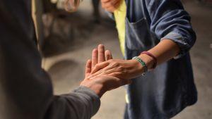 Kaksi ystävää pitelee toisiaan kädestä.