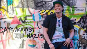 Bild av man mot stående mot vägg med graffiti