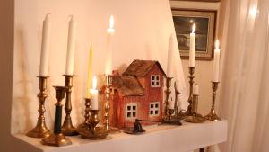 Ett miniatyrhus samt flera ljus står på spiselkransen.