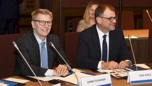 Två leende kostymklädda män bakom ett bord.