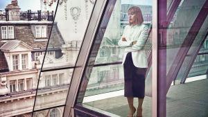 Hannah (Nicola Walker) står i sitt kontor och ser ut genom stora glasfönster.