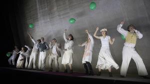 Kirsikkatarhan koko ensemble lavan etureunassa. Esirippu on kiinni, näyttelijät tanssivat vaaleissa kesäpuvuissa, vihreät ilmapallot kädessään.