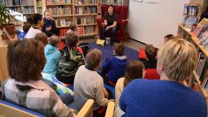 En grupp skolelever sitter i en halvcirkel runt författaren Karin Erlandsson i biblioteket i Dalsbruk.