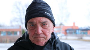 En i 70-årsåldern med en svart mössa på huvudet står på en parkeringsplats.