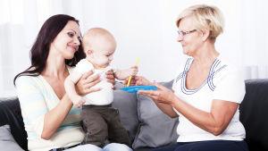 en ung kvinna sitter i en soffa, har ett litet barn i famnen, en äldre dam sitter bredvid henne och ger en leksak till barnet.