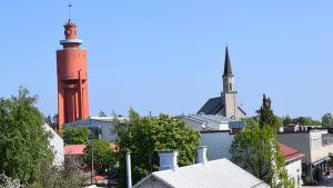 Hangö vattentorn och kyrka fotograferat från bro. Man ser hustak, gröna träd och knallblå sommarhimmel