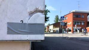 En marmorvägg där en bit marmor lossnat och den har tejpats fast med isoleringstejp. I bakgrunden syns gata, hus, cyklist. Blå himmel, sommar.