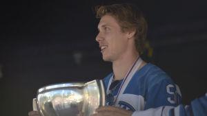 en ishockeyspelare håller i en vm-prispokal