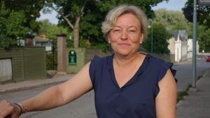 Tina Landén vid en gata och gröna träd i bakgrunden.