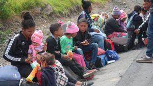 Venezuelanska familjer väntar vid vägen på gränsen mellan Venezuela och Ecuador.