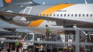 Några män lastar ett Airbus A320-flygplan tillhörande Thomas Cook vid flygplatsen Stansted.