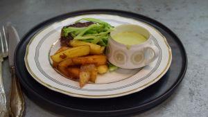 En portion med biff i fransk version med dragonemulsionsås och friterade potatisar