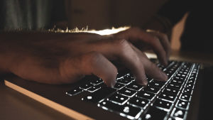 Miehen kädet kannettavalla tietokoneella.