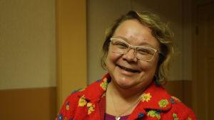 En kvinna med färggrann tröja ler.